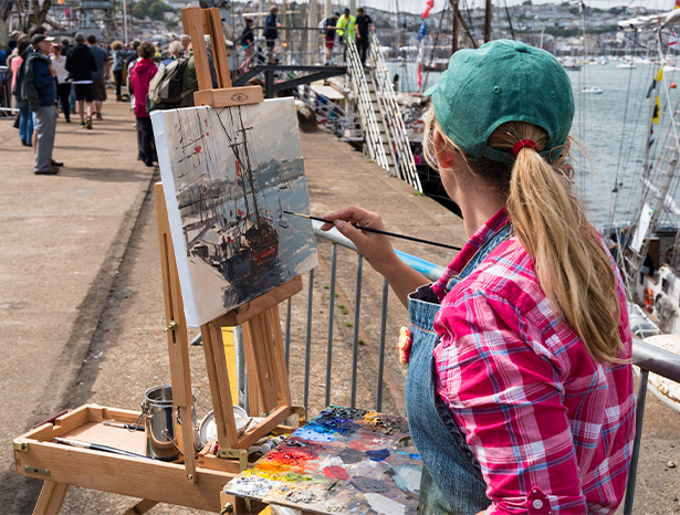 Woman painting Falmouth scene